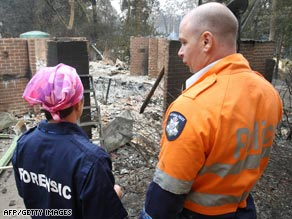 A policeman and forensics officer look over a house where five people died at Kinglake, north of Melbourne.