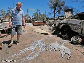Craig Kidd looks at the melted wheels of his vehicles after a fire swept his property on February 9 in Bendigo.