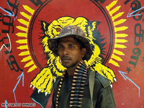A Sri Lankan soldier poses in front of a Tamil Tigers emblem in the rebel group's former military headquarters.