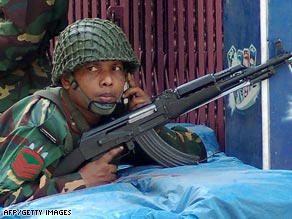 Bangladeshi soldiers take position armed with automatic weapons in Dhaka on Wednesday.