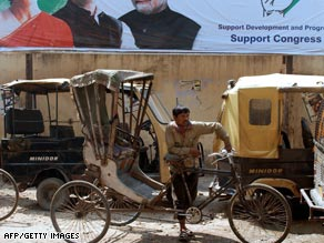 A rickshaw driver waits for customers under a Congress party poster in Dimapur, India, on Thursday.
