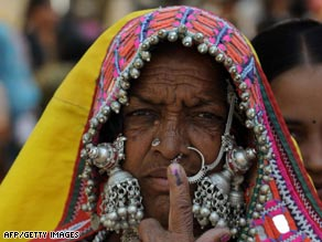 A Lambadi tribal woman shows her ink marked finger after casting her vote at Rangareddy District on April 16.