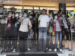 Quarantined guests and hotel employees wave through the glass at Hong Kong's Metro Park Hotel.