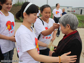 Volunteers comfort residents of Anxian temporary housing camp, most of them from Beichuan County.