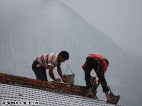 Villagers in Yaojin work on their new homes, which were funded by a U.S. organization.