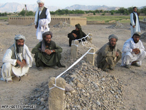 Villagers sit near the graves of victims of recent airstrikes in Garni, in western Farah province.