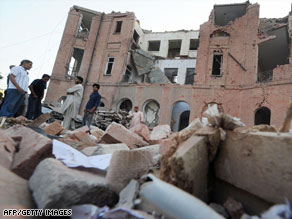 Pakistanis look Thursday at the rubble of a police building in Lahore hit by a suicide bomb on Wednesday.
