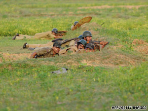 Indian paramilitary soldiers take up positions, as they proceed towards the villages of Lalgarh on Thursday.
