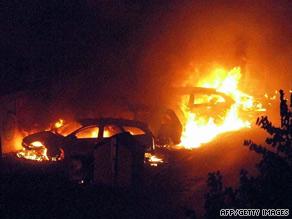 Flames engulf cars near the Viareggio railway station in western Italy on Monday.
