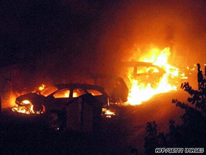 Flames engulf cars near the Viareggio railway station in western Italy on Monday.
