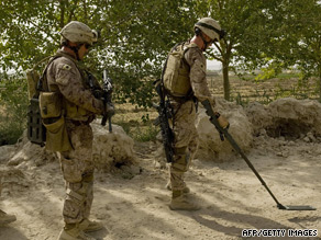 U.S. Marines scan the site of a blast which hit a U.S. vehicle in Southern Afghanistan.