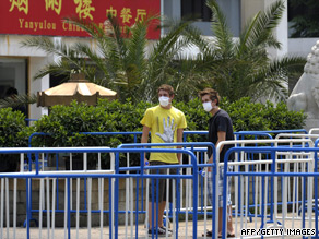 Two students outside the Yan Xiang Hotel where a group of British children and teachers have been quarantined.