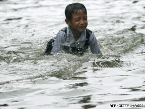 An Indian child plays in a flooded street in Mumbai earlier this month.