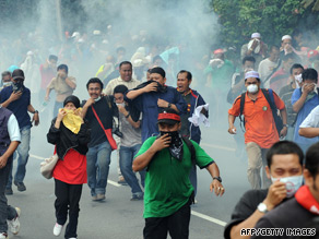 Protesters in Kuala Lumpur flee after police open fire with tear gas.
