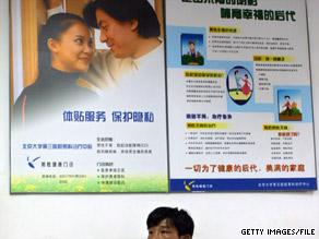 A man sits beneath fertility advertising in Beijing in 2005.