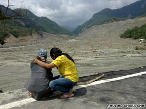 Luo Shou Luan (left) is comforted as she looks at what is left of her home village, Shiao Lin.