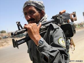 An Afghan policeman walks near the bank in Kabul where an armed robbery ended in a gun battle.