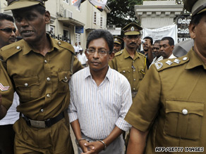 Tamil journalist J. S. Tissainayagam is led from court after being sentenced.