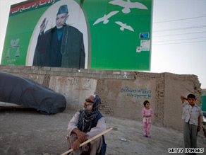 Afghans stand in front of a poster of President Hamid Karzai last week in Kabul, Afghanistan.