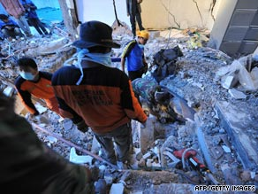 Rescuers search for victims in a collapsed building in Padang, Indonesia, on Friday.