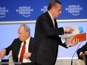 Turkish PM Recep Tayyip Erdogan leaves the stage Thursday, as Israeli President Shimon Peres sits, left.