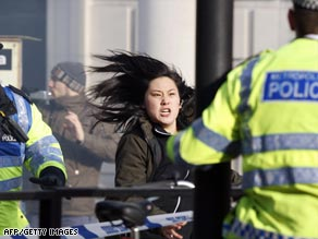 A pro-Tibet protester runs past a police cordon outside the Chinese Embassy in London.