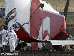 Masked investigators work at the crash site Thursday.