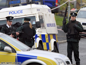 Armed police guard a grey Skoda vehicle, right in background, in which a policeman was killed in Craigavon.