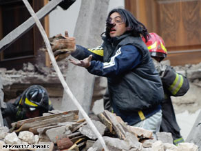 Rescue workers search for survivors in the ruins of a collapsed house in L'Aquila, Italy, early Monday.