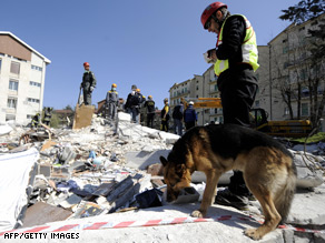 A rescuer and his dog look for survivors in L'Aquila.