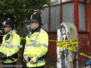 Police officers guard a house in Manchester, England, following raids and arrests of terror suspects.