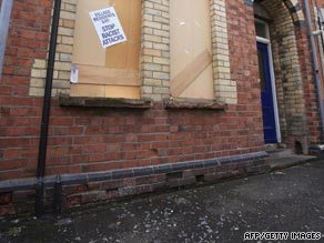 Broken glass lies next to a house in Belfast after an attack on a Romanian family.