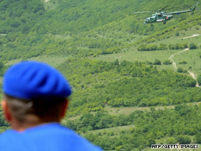 EU monitors watch a Russian helicopter flying near the border between Georgia and South Ossetia on July 29.