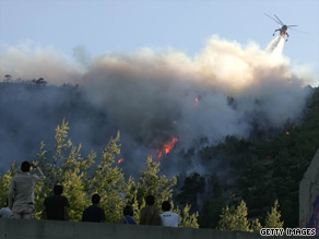 A firefighting helicopter drops water on a forest fire in the Athens suburb of Dionissii on sunday.