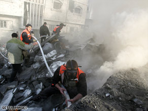 Palestinian firefighters pour water Thursday on the rubble of the home of Hamas commander Nizar Rayan.