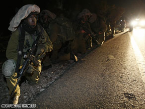 Israeli soldiers on the Israeli-Gaza border wait to enter Gaza on Saturday night.
