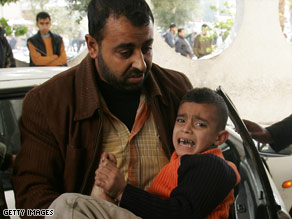 A wounded boy is carried into the Al-Shifa hospital on Monday in Gaza.