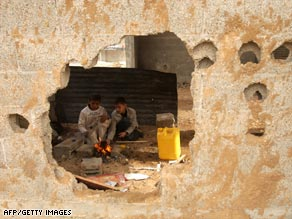 Palestinian children make coffee behind a bullet and rocket riddled wall in Rafah, Gaza, on January 24, 2009.
