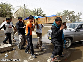 Iraqis carry a dead relative in Baghdad Sunday, the same day the U.S. said 12,000 troops will leave Iraq by fall.