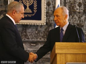 Netanyahu (left) shakes hands with Shimon Peres, who has given him more time to form a government.