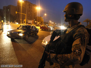 An Iraqi soldier mans a checkpoint as Iraqi troops battle Awakening Council members in Baghdad on Saturday.