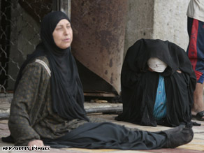 Two women grieve after the deaths of three relatives in a bombing Thursday in central Baghdad, Iraq.