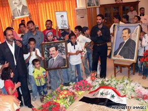 An Iraqi poet, left, gives a recital while children carry pictures of Saddam Hussein over his grave.