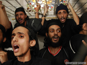 Al Qaeda suspects shout inside their courtroom cage during sentencing Monday in Yemen.