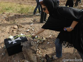 An Iranian Armenian woman places flower at crash site.