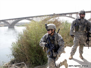 U.S. soldiers secure a Tigris River bank Sunday before the handover of a military base near Mosul to Iraqi control.