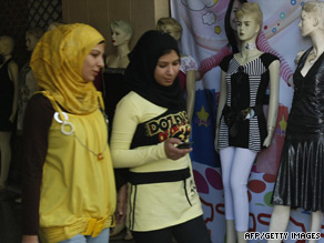 Palestinian Muslim women walk past a shop displaying Western clothes in Gaza City.