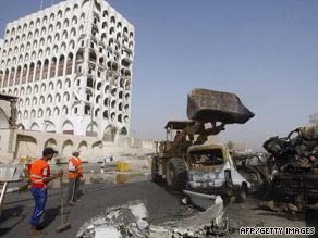 Crews clear debris from the twin bombings of the ministries of finance and foreign affairs in Baghdad.