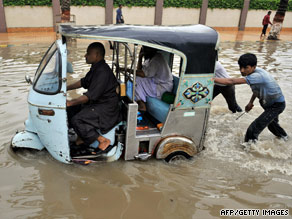 Pakistanis push a stranded auto-rickshaw along a flooded street  in Karachi on Sunday.