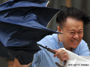 A man fights against strong winds in Hsintien, Taipei county, Taiwan, on Friday.